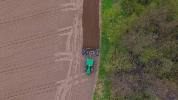 luftaufnahme von einem traktor bei der arbeit - anbau ein feld im frühjahr - landmaschinen - aerial view soil germany stock-fotos und bilder