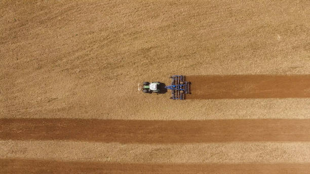 aerial view of a tractor at work on a beautiful agricultural fields in spring - top view - aerial view soil germany stock-fotos und bilder