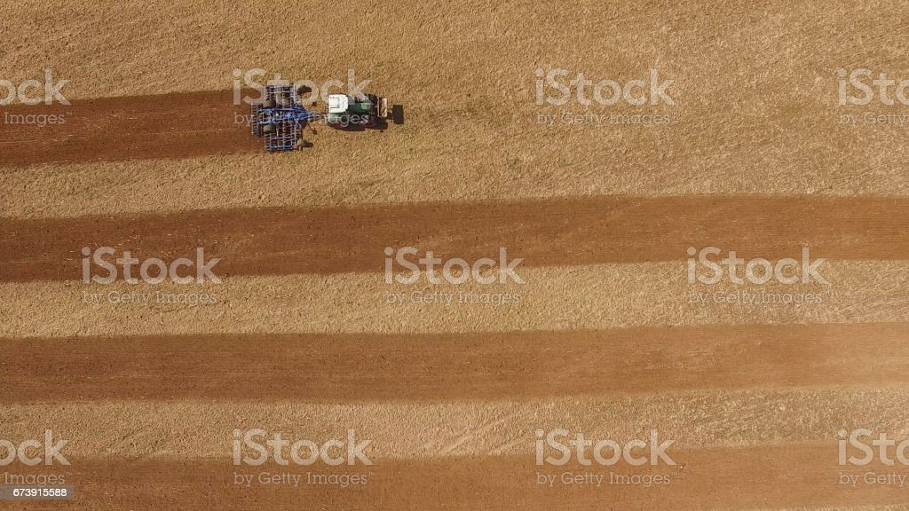 aerial view of a tractor at work on a beautiful agricultural fields in spring - top view photo libre de droits