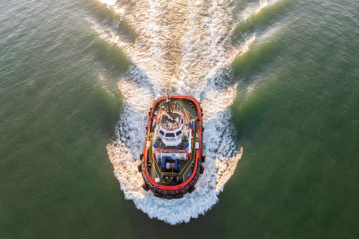 Aerial view of tugboat in leaving port for pilotting.
