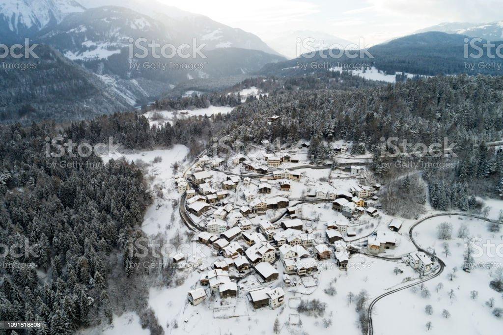 Luftaufnahme eines Dorfes im Winter in Schweizer Alpen – Foto