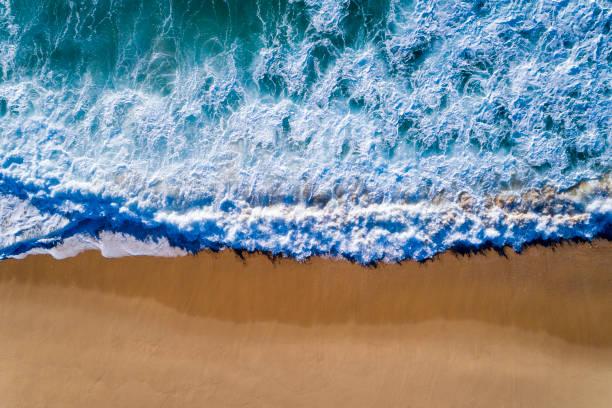 aerial view of a wave breaking at the shore of the comporta beach - setubal imagens e fotografias de stock