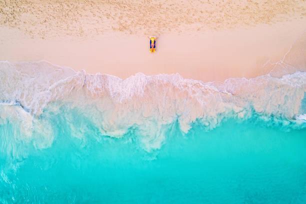 Luftaufnahme einer Frau am Strand im Bikini liegend und sonnenbadend – Foto