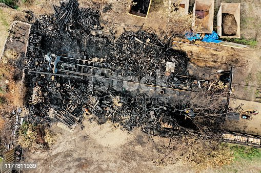 Aerial view of a wooden building completely destroyed by fire with burnt wood, perpendicular perspective