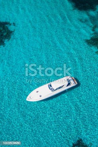 1066331604istockphoto Aerial view of a yacht on an emerald and transparent Mediterranean sea. Emerard coast (Costa Smeralda), Sardinia, Italy. 1003809680
