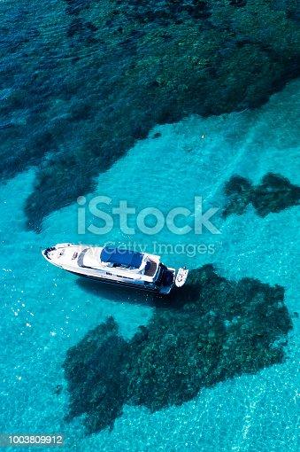 1066331604istockphoto Aerial view of a yacht on an emerald and transparent Mediterranean sea. Emerard coast (Costa Smeralda), Sardinia, Italy. 1003809912