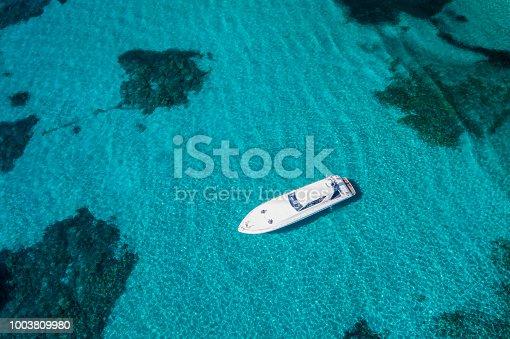 1066331604istockphoto Aerial view of a yacht on an emerald and transparent Mediterranean sea. Emerard coast (Costa Smeralda), Sardinia, Italy. 1003809980