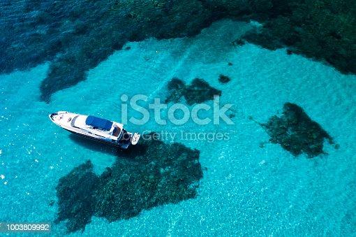 1066331604istockphoto Aerial view of a yacht on an emerald and transparent Mediterranean sea. Emerard coast (Costa Smeralda), Sardinia, Italy. 1003809992