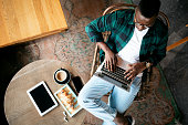 istock Aerial view of a young African American man working on his laptop 1273523957