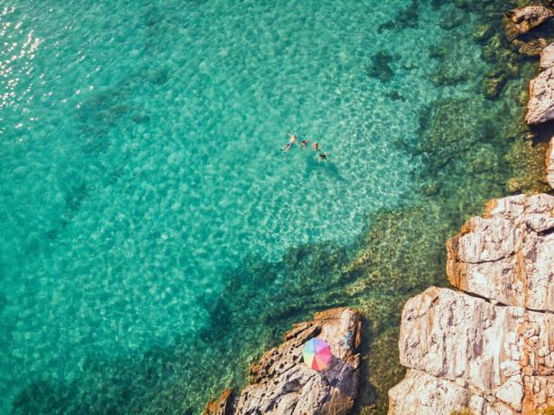 Luftaufnahme einer jungen Familie, die am schönen Strand auf der griechischen Insel schwimmt und schwimmt – Foto