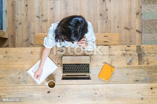 istock Aerial view of a young woman studying at home 629303732