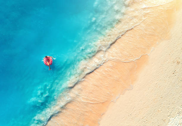 aerial view of a young woman swimming with the donut swim ring in the clear blue sea with waves at sunset in summer. tropical aerial landscape with girl, azure water, sandy beach. top view. travel - den belitsky foto e immagini stock