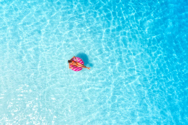 Aerial view of a young woman swimming with the pink donut swim ring in transparent blue sea at sunset in summer. Tropical aerial landscape with girl, clear azure water, sandy beach. Top view. Travel stock photo