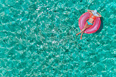 Aerial view of a young women relaxing on inflatable ring in a tropical turquoise pristine beach. Los Juanes, Morrocoy, Venezuela