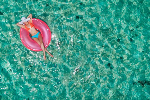 Vue aérienne d'une jeune femme détendant sur l'anneau gonflable dans une plage immaculée turquoise tropicale - Photo