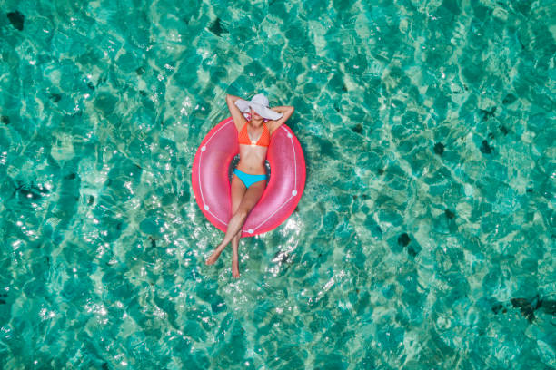 Aerial view of a young women relaxing on inflatable ring in a tropical turquoise pristine beach stock photo
