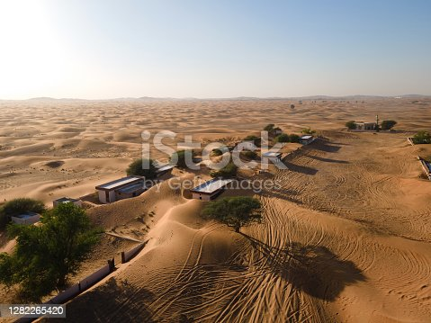Aerial view of ghost village and abandoned houses in the UAE desert in Al Madam in Sharjah emirate near Dubai, overtaken by sand dunes which are covering and entering house remaining