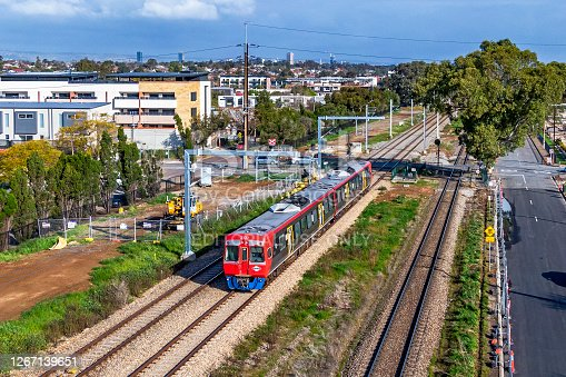 Adelaide, Australia - August 19, 2020: Aerial view of Adelaide Metro broad gauge diesel commuter train passing under new electrification works in inner northern suburbs of Adelaide. The interstate standard gauge line is in the right of frame.