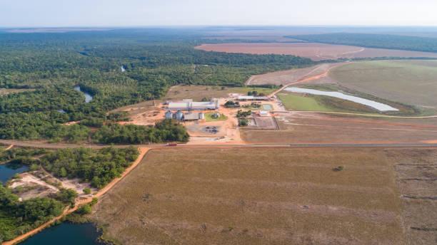 Luftaufnahme der landwirtschaftlichen Landschaft mit einem großen Bauernhof, Grenze zum verbleibenden Regenwald, Zeichen der Entwaldung, San Jose do Rio Claro, Mato Grosso, Brasilien – Foto