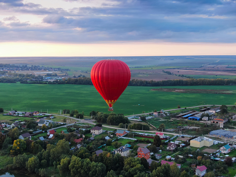 Aerial view of air balloons flights from altitude in summer above the river. Drone panorama. Beautiful landscape scene.