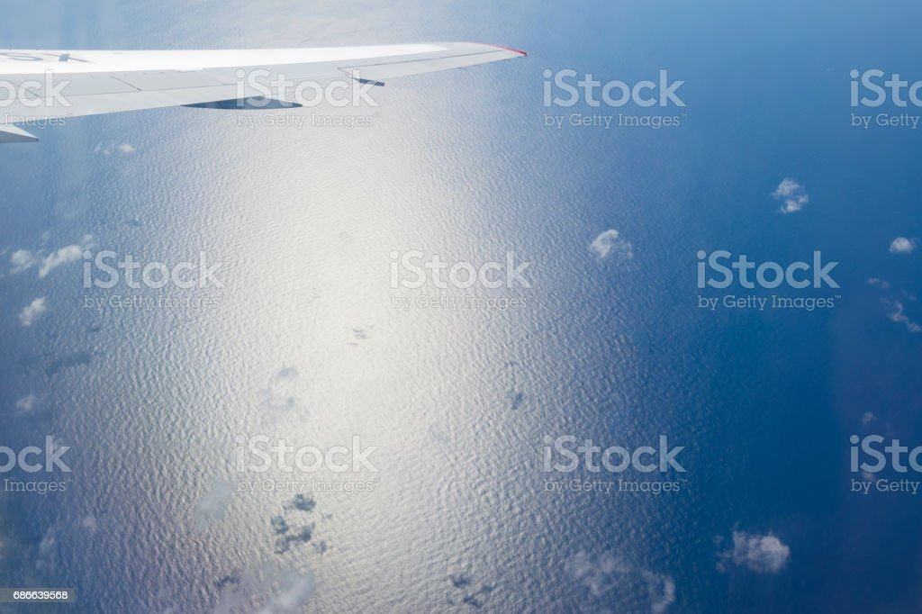 Aerial view of airplane wing over blue tropical ocean royalty-free stock photo
