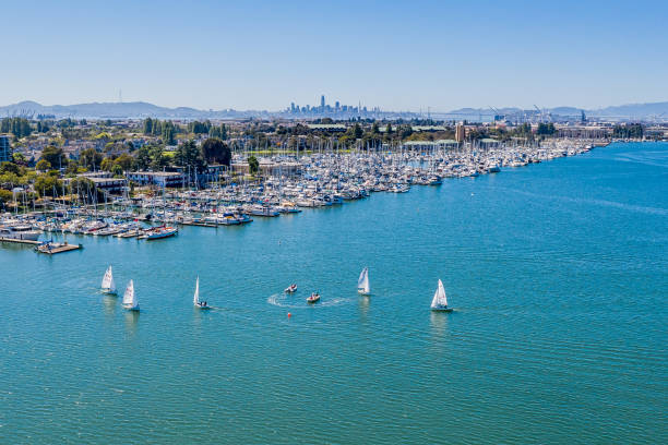 Aerial view of Alameda and Oakland Harbor An aerial view of Alameda, Alameda Point , the skyline of San Francisco across the Bay and sailboats in the bay. A beautiful blue sky on a sunny day. The harbor is bustling with activity. alameda california stock pictures, royalty-free photos & images