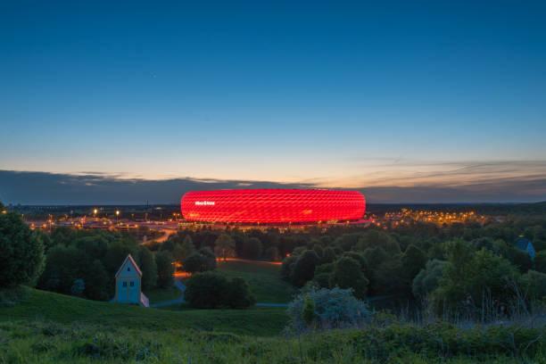 luftbild der allianz arena, dem fußballstadion des fc bayern, bei der dämmerung von fröttmanninger berg in rot beleuchtet - bayern fußball heute stock-fotos und bilder