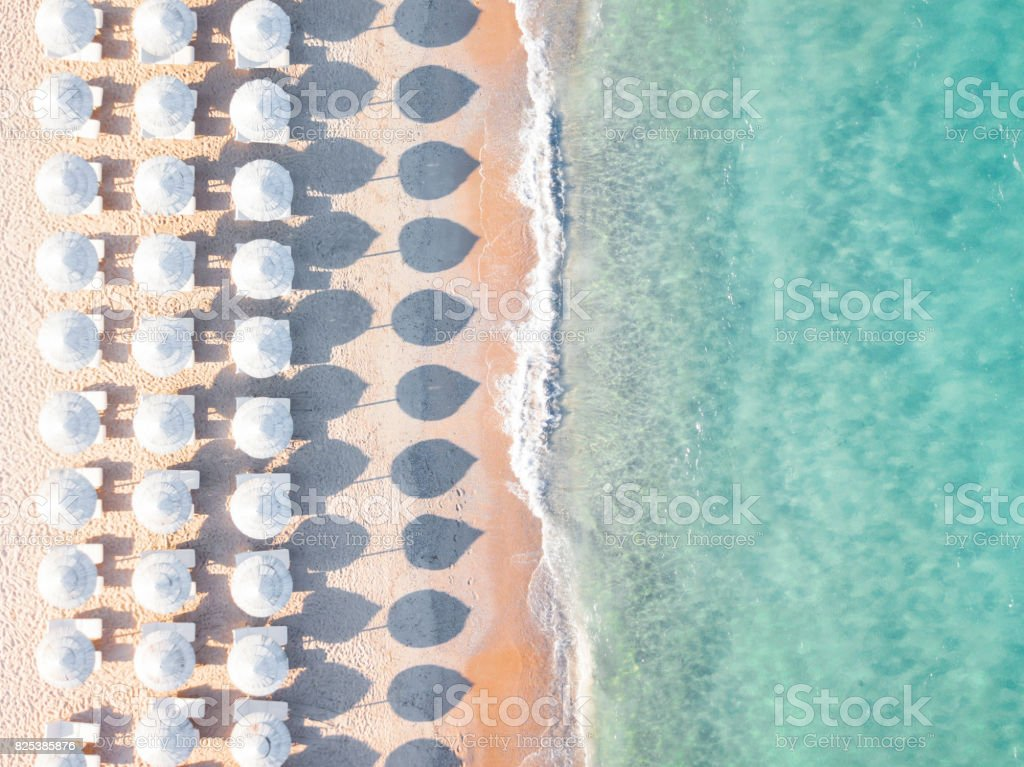 Aerial view of amazing beach with white umbrellas and turquoise sea at sunset. Mediterranean sea, Sardinia, Italy. royalty-free stock photo