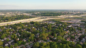 istock Aerial view of american suburb, highway at summertime.  Establishing shot of american neighborhood. Real estate, residential houses, freeway, traffic. Drone shot, from above 1247945395