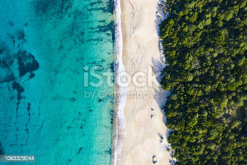 Aerial view of an amazing wild beach bathed by a transparent and turquoise sea. Sardinia, Italy.