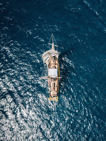 Aerial view of an ancient sailing ship over blue water. Mediterranean sea.