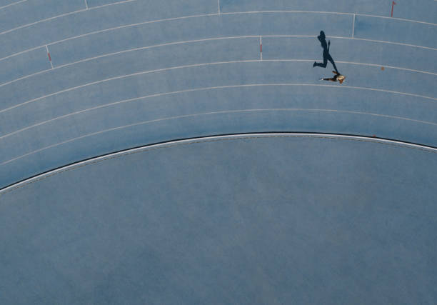 Aerial view of an athlete running on track Sprinter running on athletic track. Top view of a sprinter running on race track in a stadium with shadow falling on the side. women's track stock pictures, royalty-free photos & images