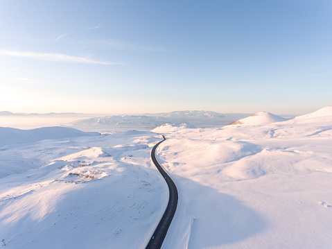 Empty curved road at winter season in between mountains