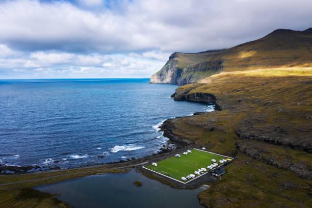 luchtfoto van een oud voetbalveld aan de kust bij eidi in faeröer - faeröer stockfoto's en -beelden