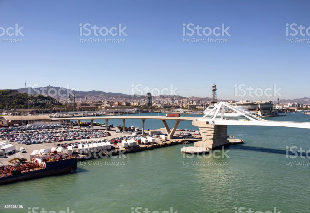 Aerial view of Barcelona port. Big cruise ship is waiting to depart. Many cars and containers to be shipped. Modern bridge and the city are in the view. stock photo