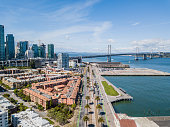 An aerial view of the Bay Bridge on a sunny day. A view from above the Embarcadero. Luxury residential area and skyscrapers along the Embaradero.