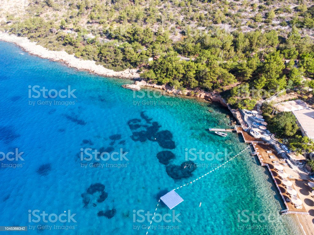 Aerial View of Beach Cove with Sunbeds, Blue Turquoise Sea and Trees stock photo