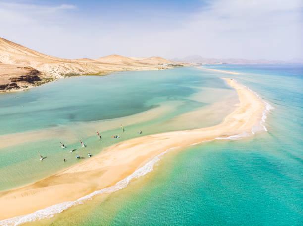 Luftaufnahme des Strandes auf der Insel Fuerteventura mit Windsurfern, die in den Sommerferien Windsurfen in blauem türkisfarbenem Wasser lernen, Kanarische Inseln von der Drohne – Foto