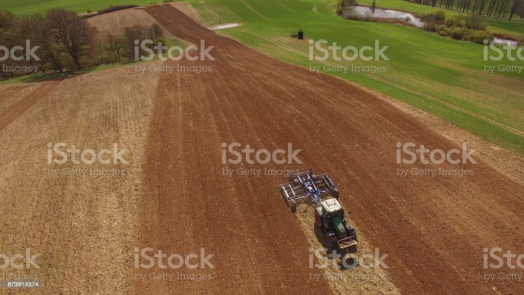 Aerial view of beautiful agricultural fields in spring with a tractor at work - cultivating a field photo libre de droits