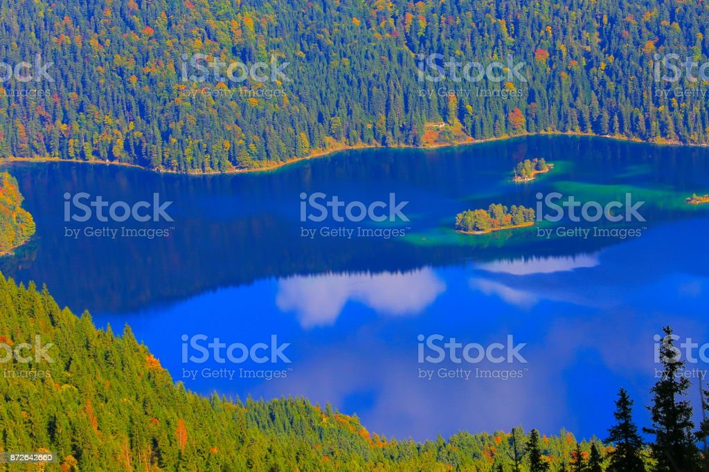 Aerial view of Beautiful and idyllic Eibsee alpine turquoise lake with reflection at gold colored sunrise, view from above Zugspitze mountain peak – dramatic and majestic landscape in Bavarian alps, gold colored autumn  – Garmisch, Bavaria, Germany stock photo