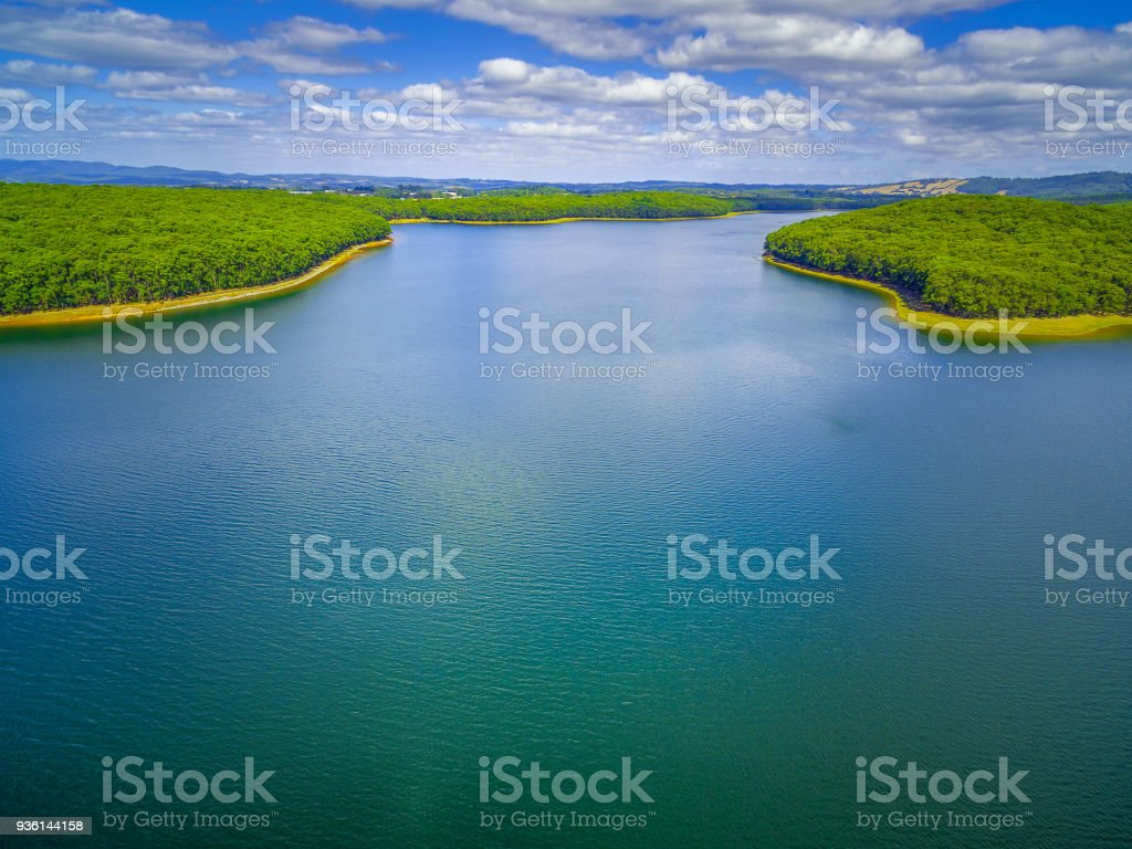 Aerial view of beautiful blue lake and forest under white fluffy clouds in Australia stock photo