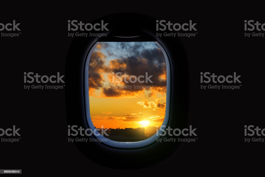 Aerial view of beautiful bright sunset sky and rainy clouds from airplane window. stock photo