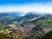 Color photography of high angle view, aerial view of beautiful French natural landscape in Bugey mountains, with small town of Culoz, the Rhone River and famous Lake Bourget in background. Shot from Grand Colombier mountain top during a sunny summer day, in Bugey mountains, in Ain department not far from Jura and Savoie border near Culoz city, Auvergne-Rhone-Alpes region in France (Europe).