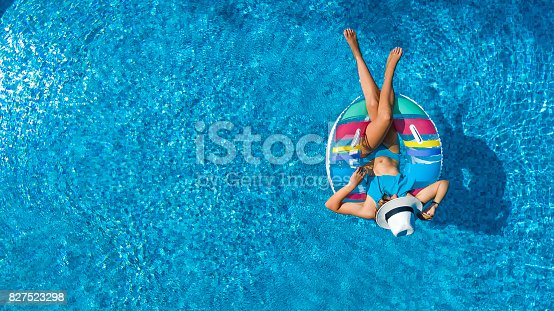 istock Aerial view of beautiful girl in swimming pool from above, swim on inflatable ring donut and has fun in water on family vacation 827523298