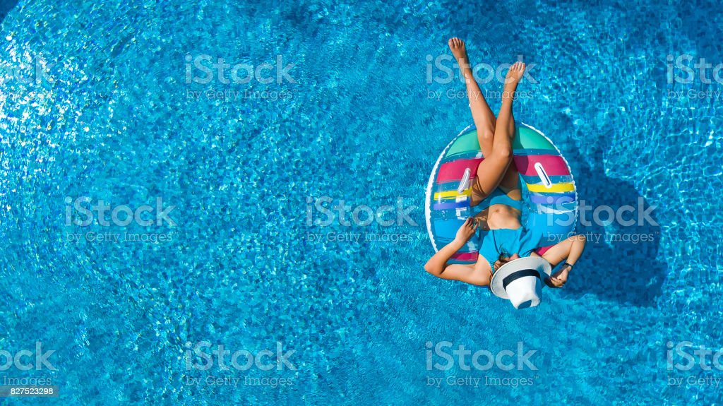 Aerial view of beautiful girl in swimming pool from above, swim on inflatable ring donut and has fun in water on family vacation stock photo