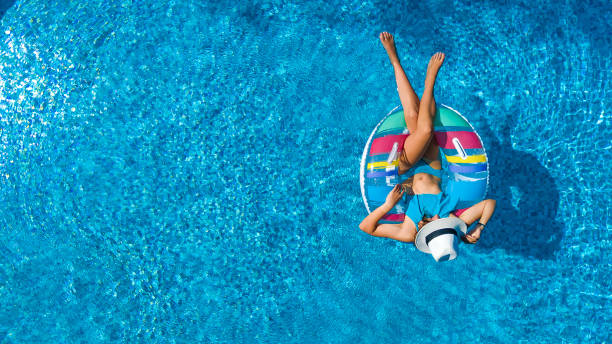 aerial view of beautiful girl in swimming pool from above, swim on inflatable ring donut and has fun in water on family vacation - vacanze foto e immagini stock