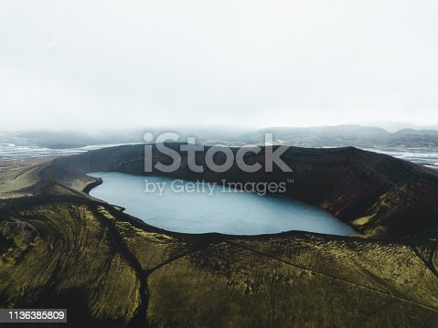 Drone photo of foggy volcanic landscape and lake in Iceland