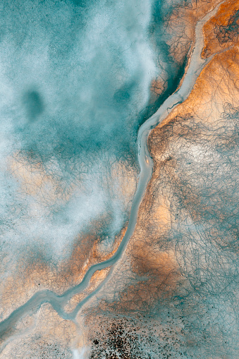 Aerial view of beautiful natural shapes and textures on lake which looks like an abstract painting. Taken via drone.