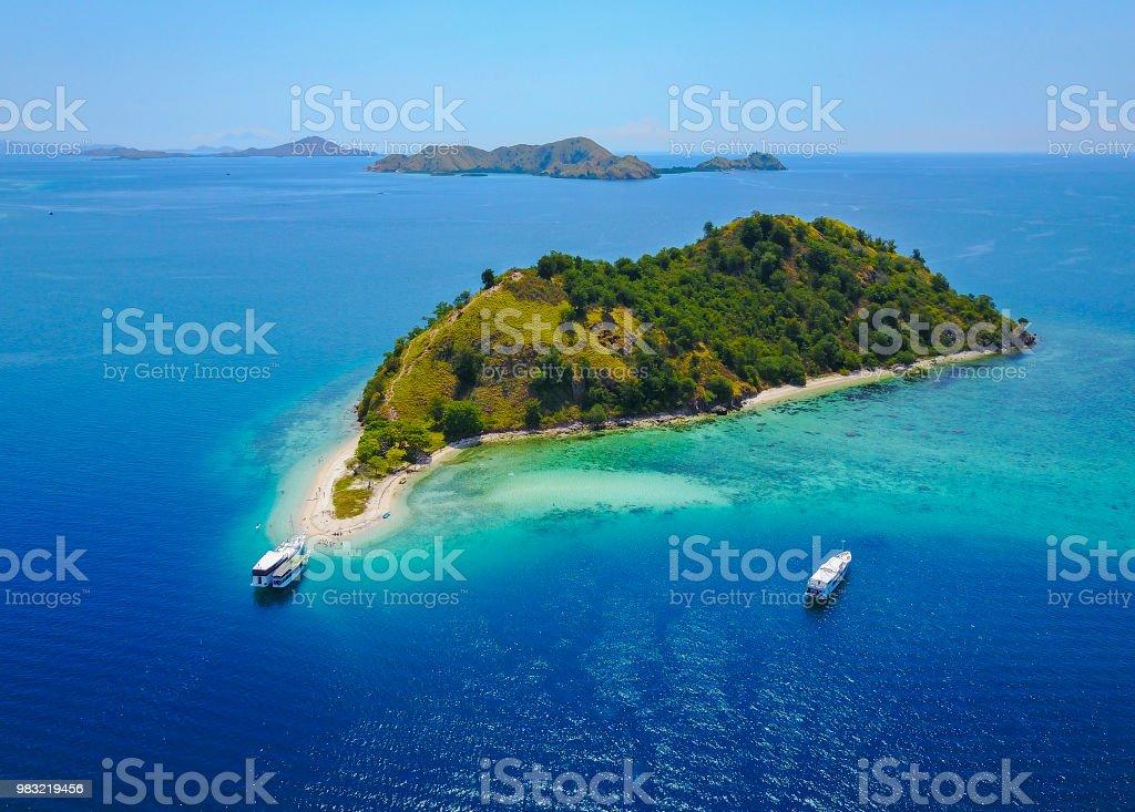 Luftaufnahme der schönen Landschaft auf der Insel Flores mit touristische Yacht, Türkis und dunklen Blau des Meeres. – Foto