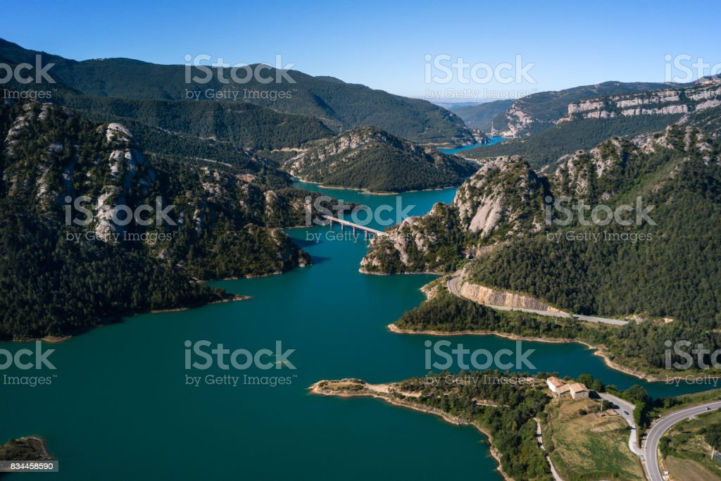 Aerial view of beautiful turquoise lake in mountains and bridge across it. stock photo